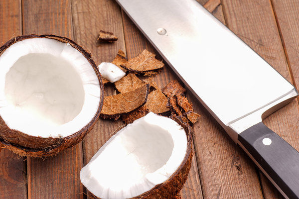 Coconut, broken and open ready for eating on wood board http://cleanfoodcrush.com/coconut-oil-benefits-part1