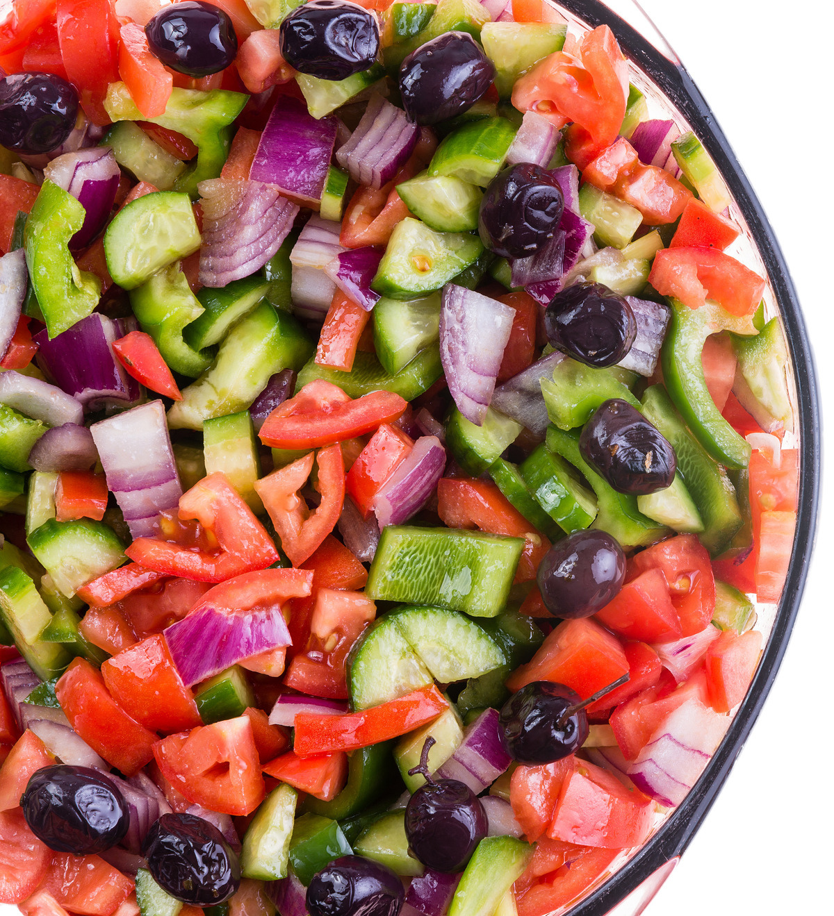 Colorful healthy Turkish shepherd salad with assorted diced fresh vegetables served in a round bowl view close up from overhead over white with copy space on the right