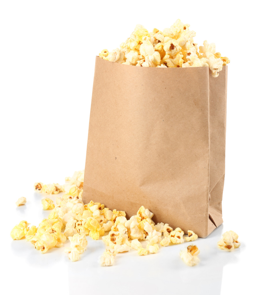 Popcorn in paper bag isolated on white https://cleanfoodcrush.com/diy-popcorn-bags